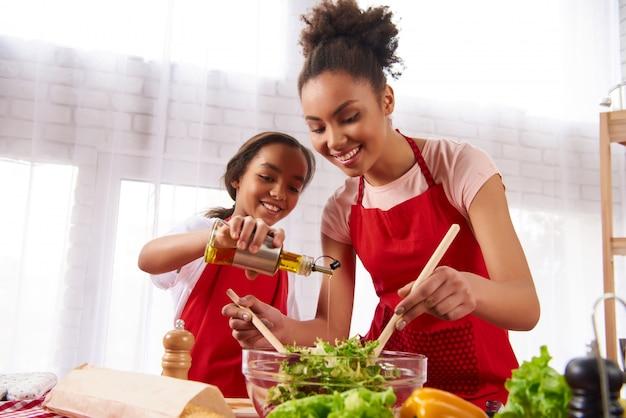 小さな娘がオリーブオイルをサラダに注ぐ