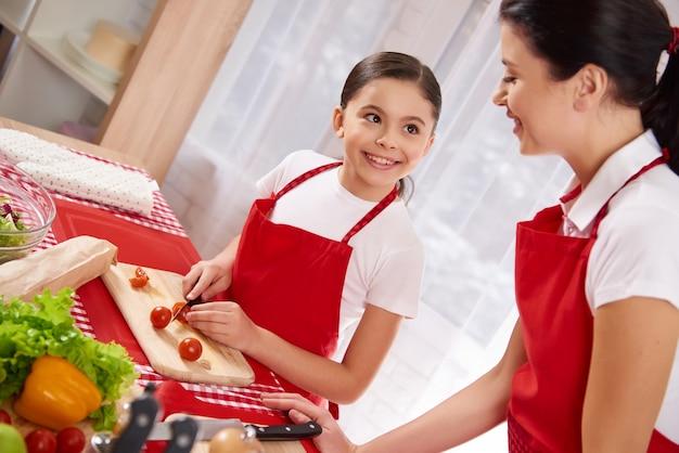 少女が台所でトマトをスライスします。