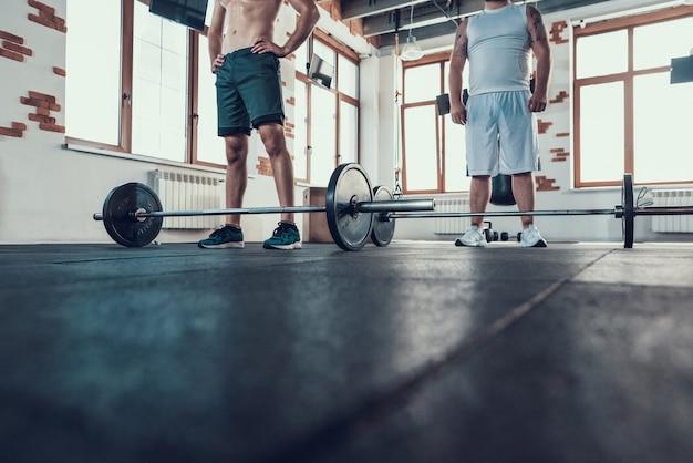 Два больших парня стоят в спортзале перед решеткой.