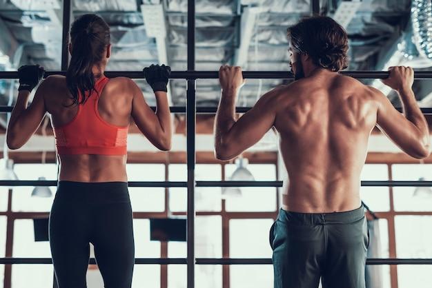Парень и девушка делают подтягивания в тренажерном зале.
