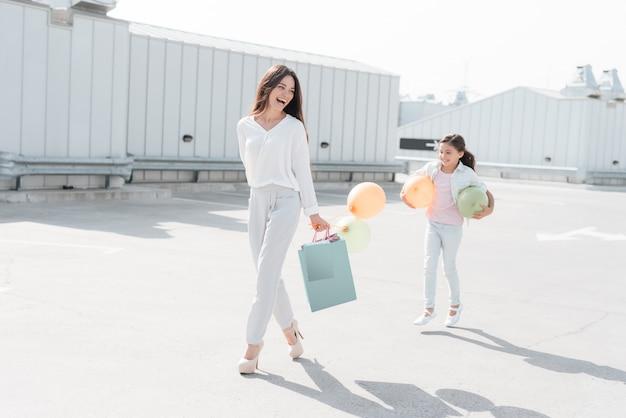 母と娘の買い物袋が歩いています。