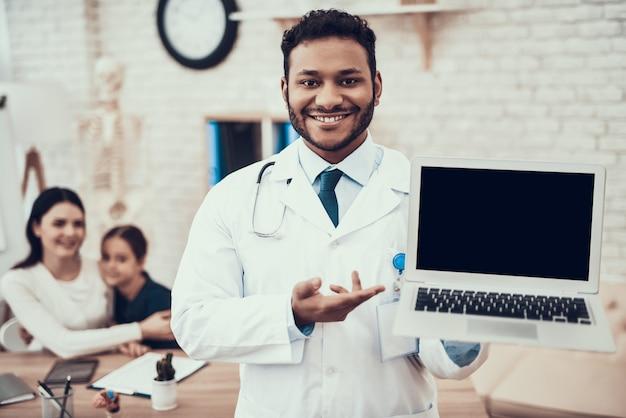 医者は母と娘と一緒にノートパソコンでポーズします。