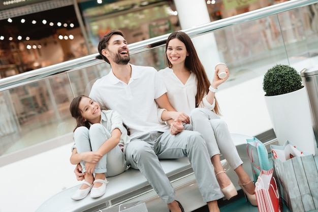 Отец, мать и дочь сидят на скамейке в торговом центре.