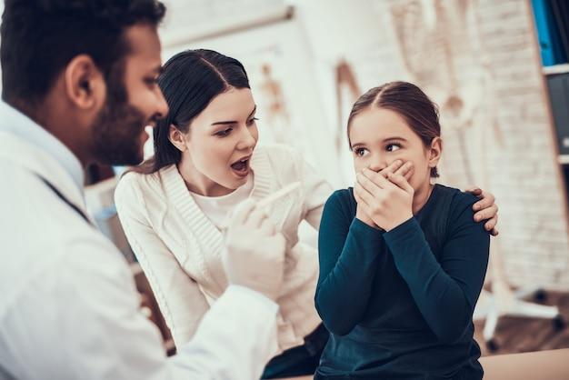 女の子ののどを調べますが、娘は拒否しています。
