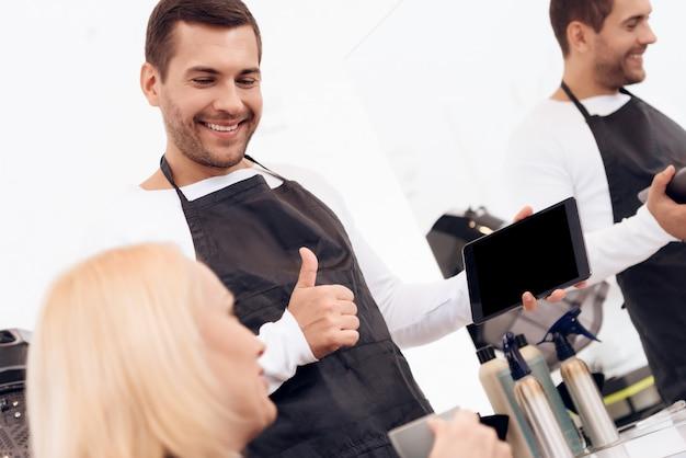 美容師は、タブレット上の女性の散髪を選択します。