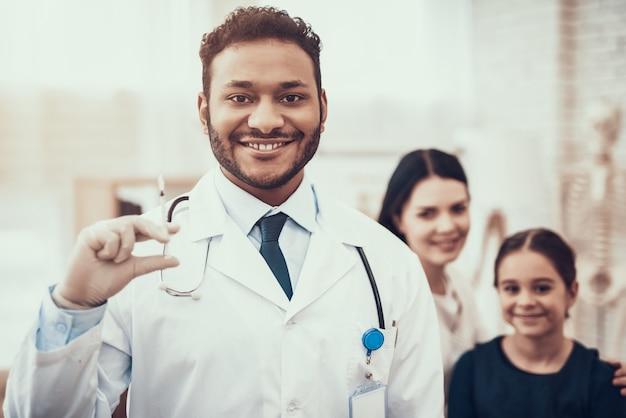 医者は母と娘と一緒に注射器でポーズします。