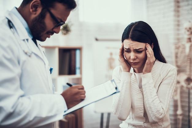 Доктор слушает симптомы женщины. у женщины болит голова.