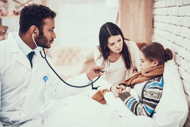 医者は聴診器を使用しています。妊娠中の母親と娘
