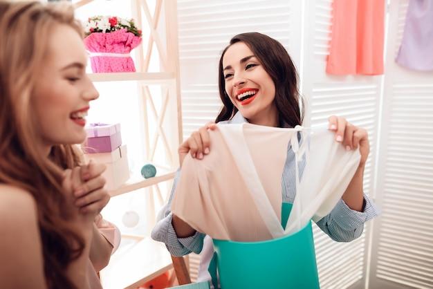 Две девушки по магазинам. девушки выбирают одежду в магазине.