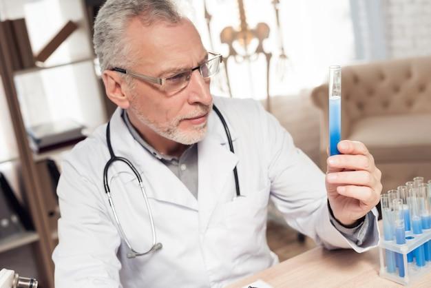 医者は顕微鏡と聴診器で机に座っています。