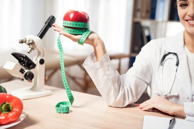 Женщина держит красное яблоко с измерительной ленты.