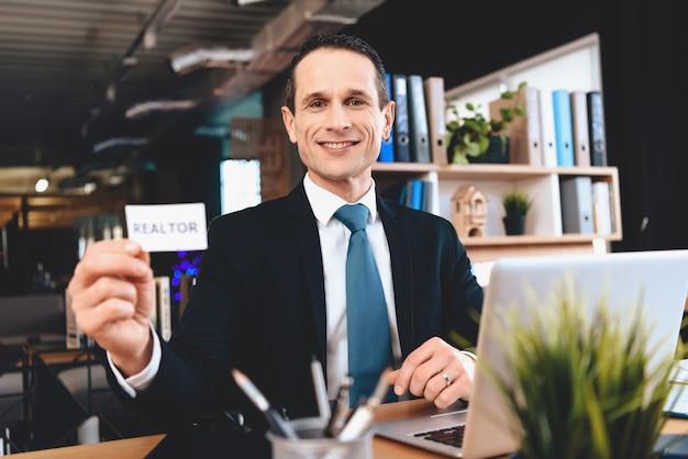 ビジネスカードを机に座って笑顔の全米リアルター協会加入者。