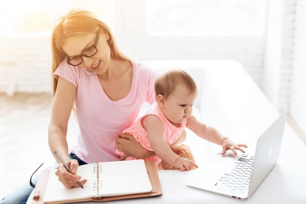 スマートフォンを使用して作業している赤ちゃんと母親。