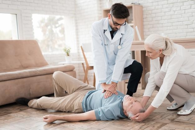 Врач скорой помощи делает слр для пожилого человека.