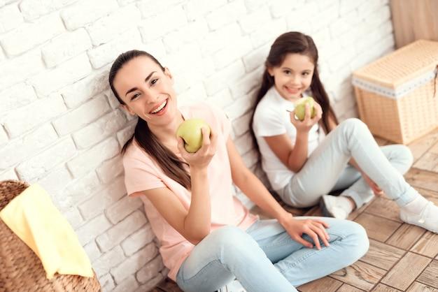 ママと娘はリンゴで床に座っています。