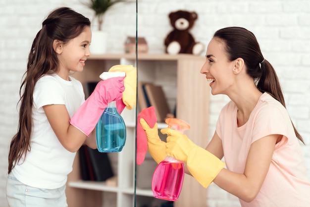 娘と母は洗剤でガラスを拭きます。