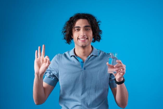 Ближневосточный мужчина позирует с водой и знак ок.