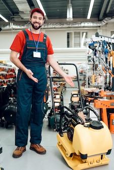電動工具店のプレートコンパクターを持つセールスマン