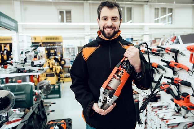 セールスマンは、電動工具店でディスクグラインダーでポーズを取っています。