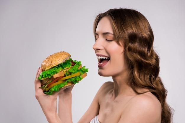 美しい少女は大きなハンバーガーを食べる。