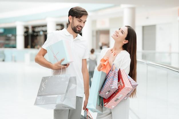 買い物袋を持つ男女が歩いています。