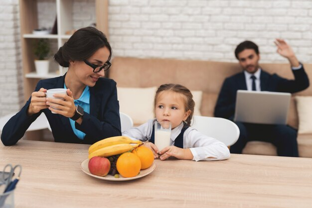 Счастливая мама пьет чай, а обиженный ребенок пьет молоко