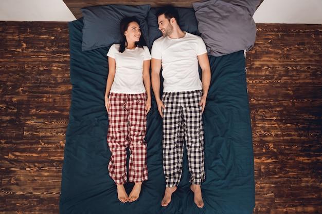 Пара лежит на кровати и смотрит друг на друга