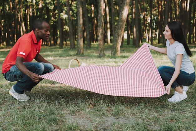 幸せなカップルは、ピクニックのテーブルクロスを広げます。