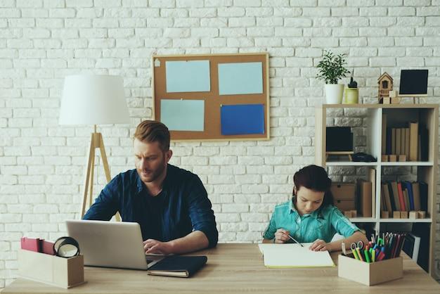 少女が勉強している間、パパはコンピューターで働いています。