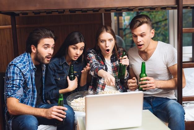 Юноши и девушки смотрят фильм на ноутбуке с пивом.
