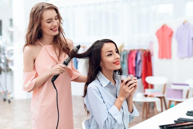 若い女の子はショールームでヘアスタイリングをする。