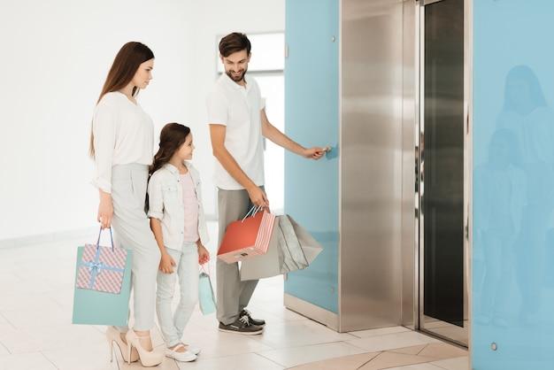 家族は買い物でいっぱいの袋でショッピングモールを出る