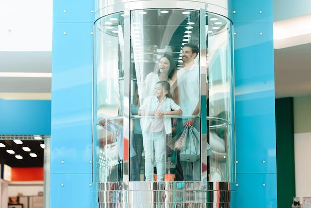 Семья спускается в лифте в торговом центре