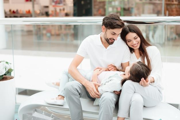 家族はショッピングモールのベンチに座っています。