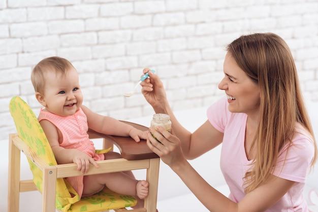 Улыбающаяся мама с пюре, кормящая улыбающегося ребенка