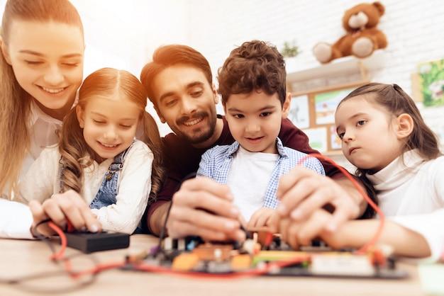 先生と一緒にいる子供たちは、はんだごてで働きます。