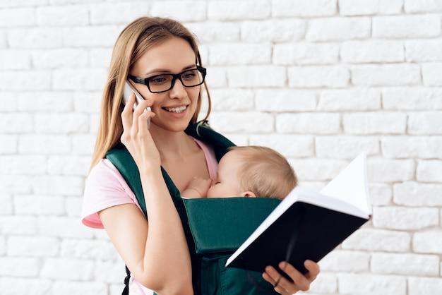 ビジネスの女性が電話を話していると新生児を保持