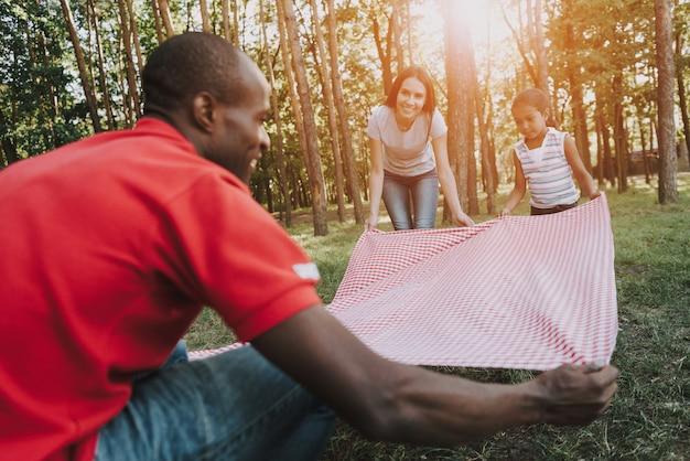 ピクニックのための多国籍家族の広がりのテーブルクロス。