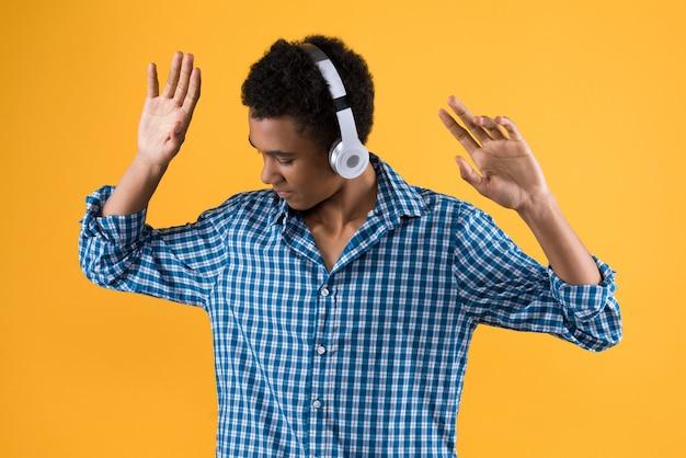 ヘッドフォンの踊りで幸せなアフロアメリカンティーンエイジャー