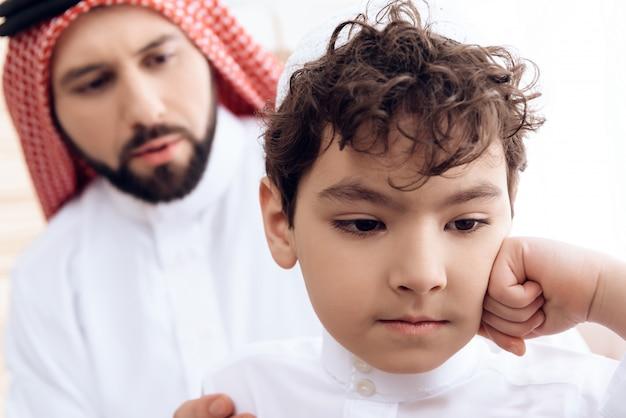 アラブ人は小さな気分を害する息子から許しを求めます。