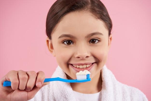 バスローブの少女は歯を磨いています。