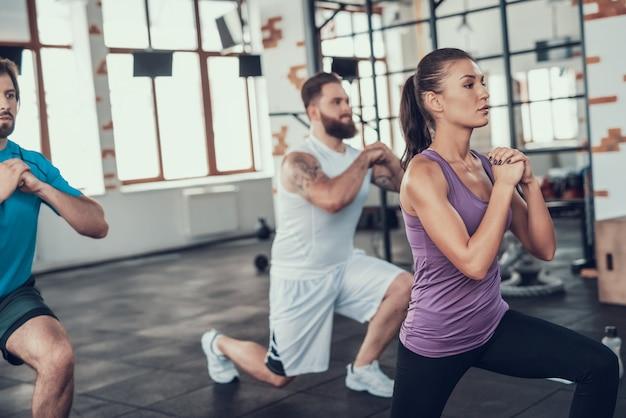 Девочка и двое парней делают упражнения выпад в тренажерном зале.