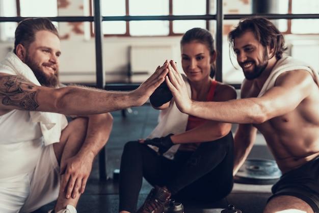 Отдыхающие спортсмены дают высокие пять друг другу.