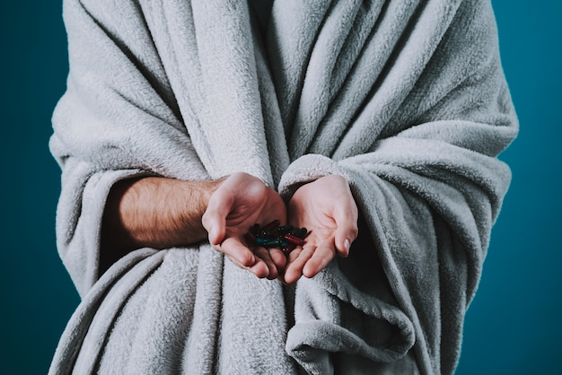 男は風邪をひいて、青い背景に分離された丸薬を食べます。