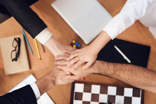 人々はテーブルの上の腕を交差します。
