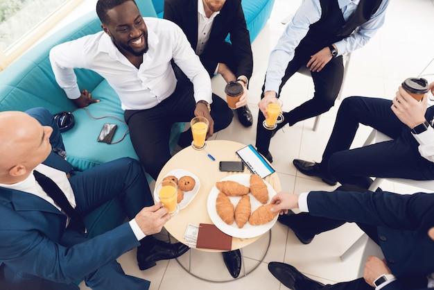 Мужчины обедают в зале ожидания в аэропорту вместе.