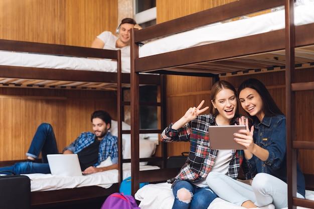 Девушки сидят на кровати и разговаривают по видео на планшете.