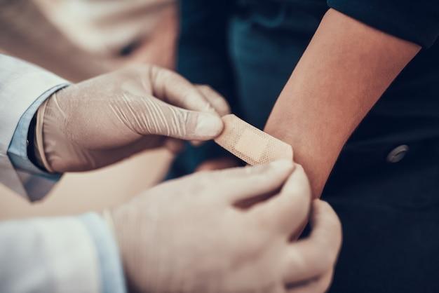 医者は小さな女の子の腕にパッチを当てています。