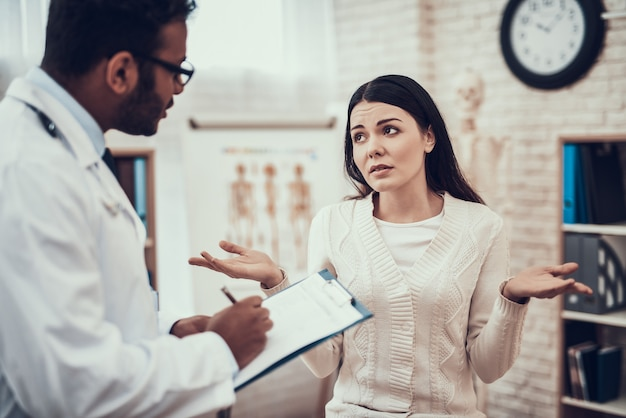 Доктор слушает симптомы женщины.