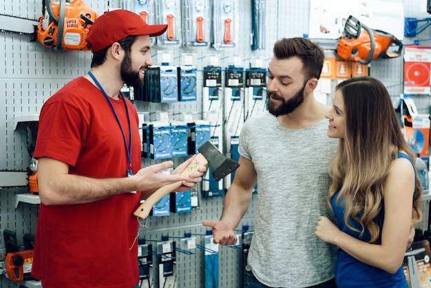 電動工具店でクライアントの新しい斧のカップル。